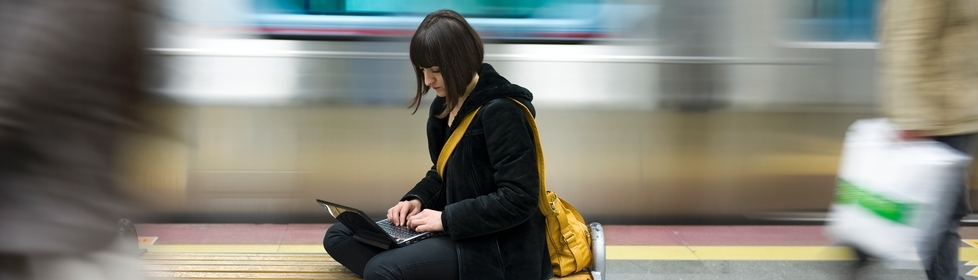 Lady using laptop in train station